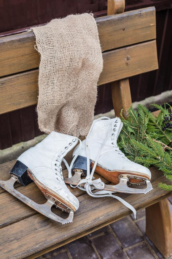 Pair of vintage white Ice Skates lying on the bench with fir-tree branches. Toned stock photo