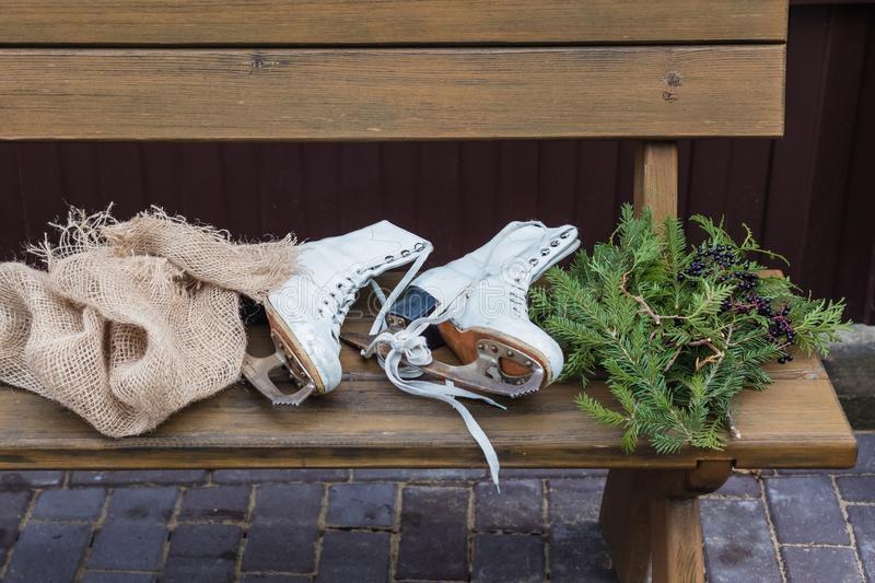 Pair of vintage white Ice Skates lying on the bench with fir-tree branches. Toned royalty free stock photo