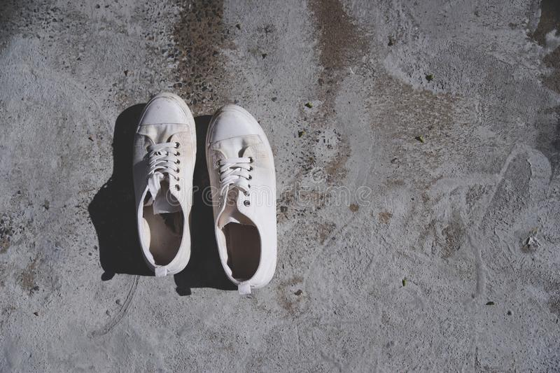 A pair of vintage white sneaker or shoes on cement ground floor stock photography
