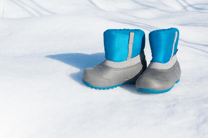 Pair of waterproof children boots on the snow. Space for text stock images