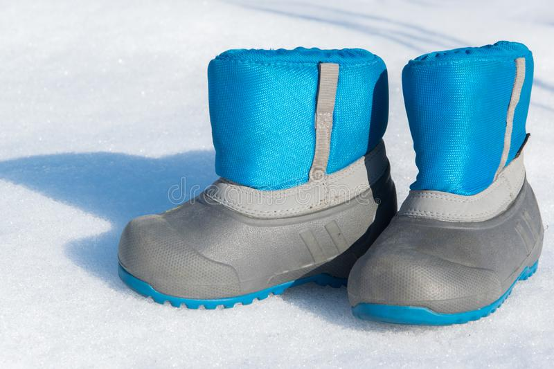Pair of waterproof children boots on the snow. Space for text royalty free stock photography