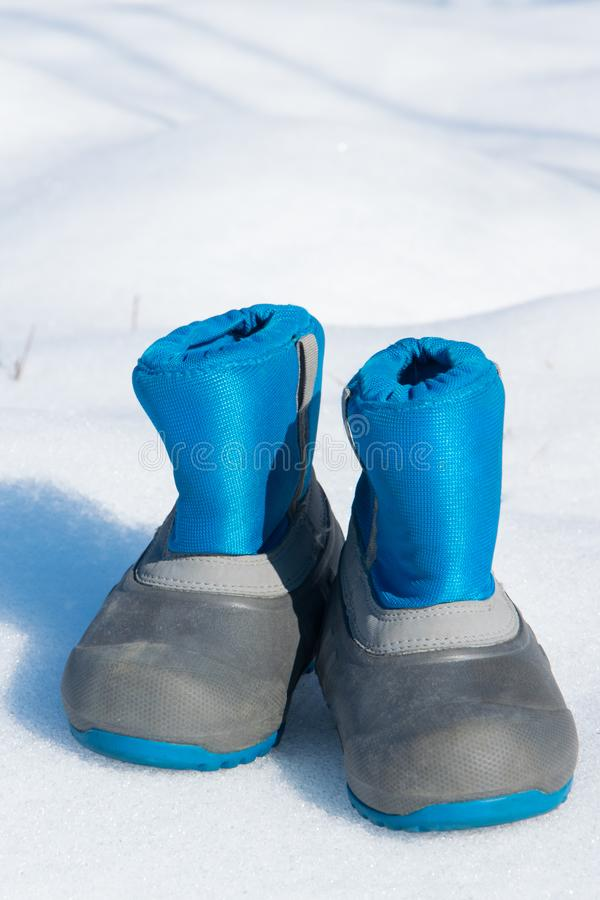 Pair of waterproof children boots on the snow. Space for text royalty free stock photo