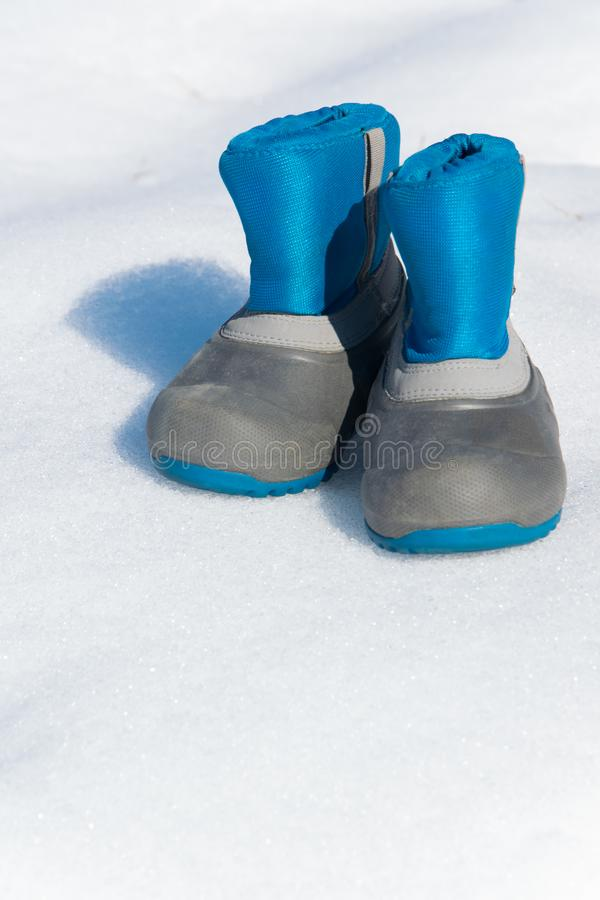 Pair of waterproof children boots on the snow. Space for text stock image