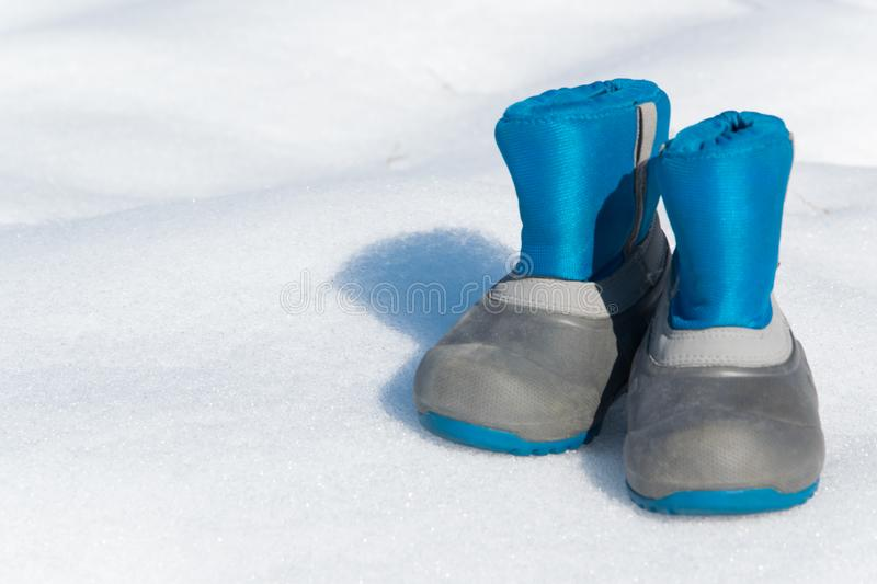 Pair of waterproof children boots on the snow. Space for text royalty free stock image
