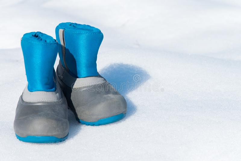 Pair of waterproof children boots on the snow. Space for text royalty free stock images