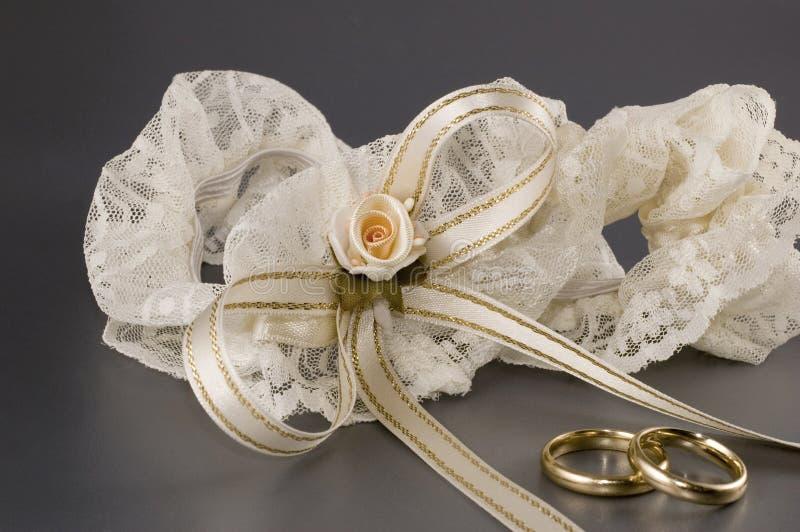 A pair of wedding rings and a garter. Bridal garter with a pair of wedding rings royalty free stock photos