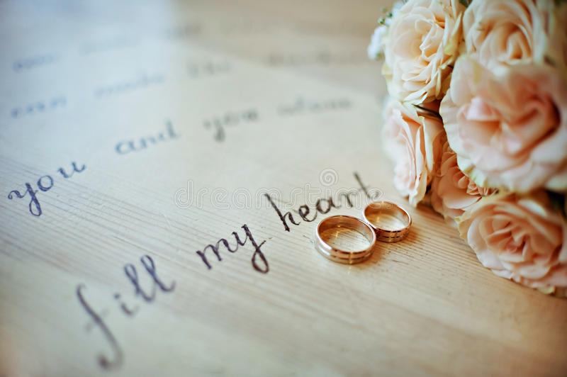 Pair of wedding rings in warm colors, with a bouquet yellow roses stock image