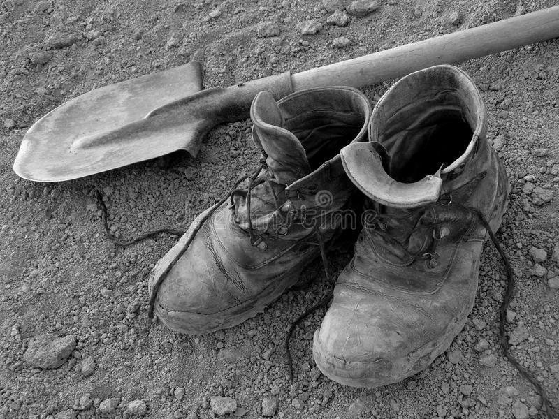 Pair of well worn work boots. And spade on the ground royalty free stock images