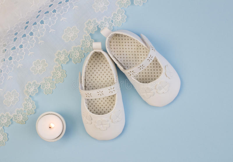 Pair of white baby booties on blue background with lace christen stock photography