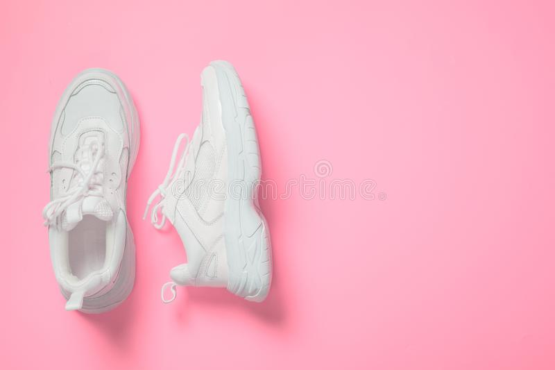 Pair of white female trendy sneakers on pink. Flat lay, top view minimal background royalty free stock image