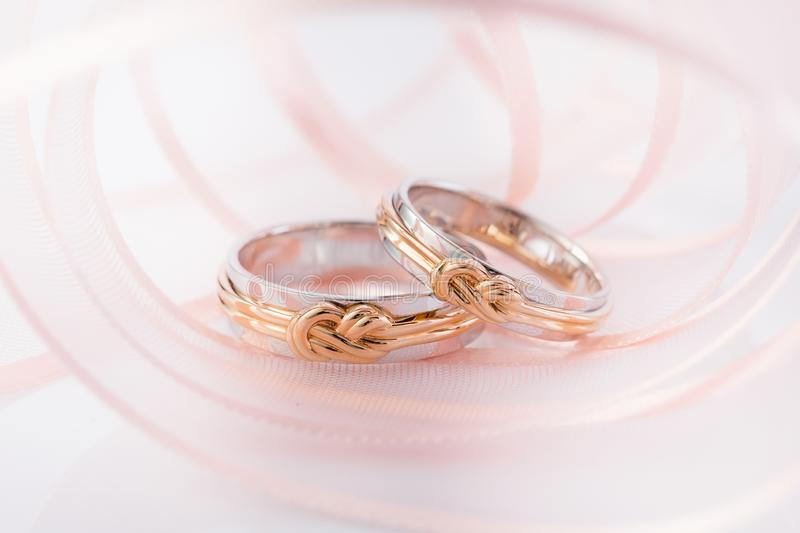 Pair of white gold wedding rings with pink gold knot on pink background stock photos