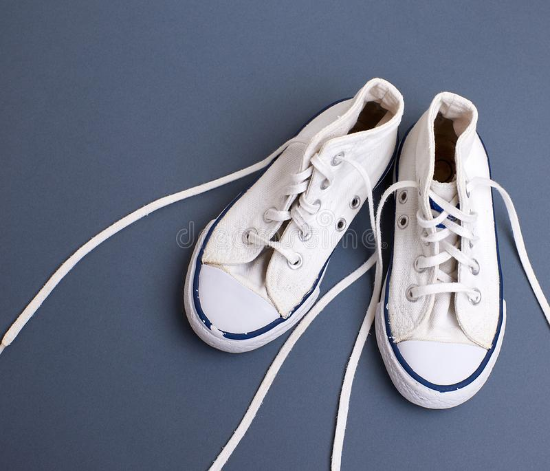 Pair of white old textile sneakers with untied laces. On a blck background, top view royalty free stock photo
