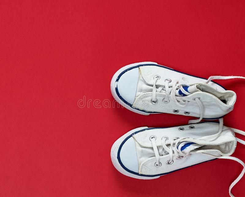 Pair of white old textile sneakers with untied laces. On a red background, top view stock photography