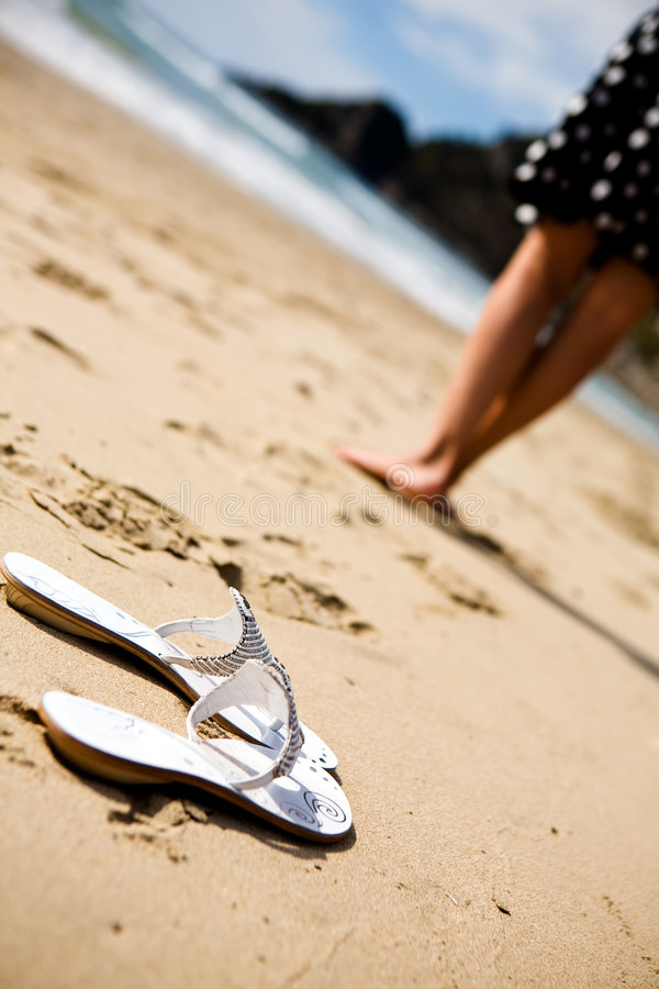 A pair of white sandals on the sand stock photography