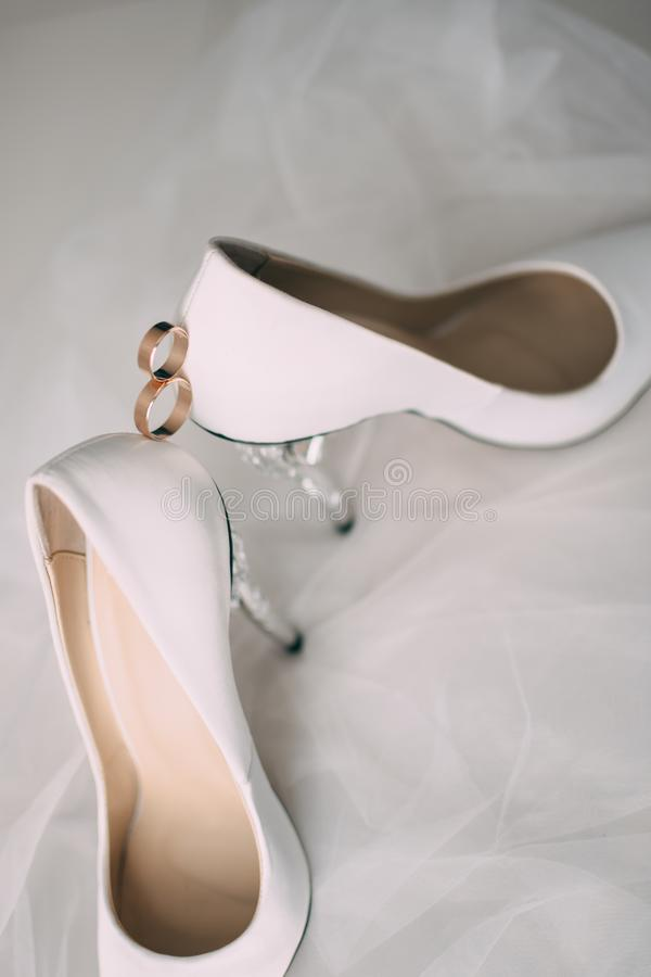 A pair of white wedding shoes with rings on a stool. royalty free stock photos