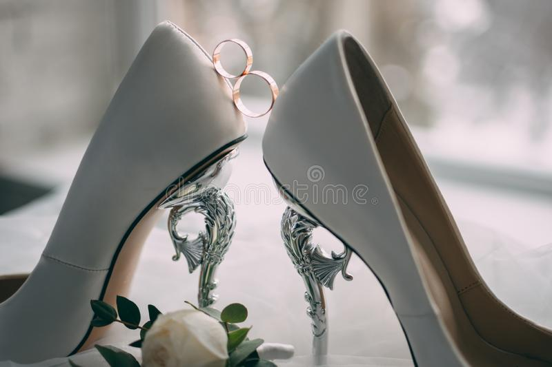 A pair of white wedding shoes with rings on a stool. stock photo