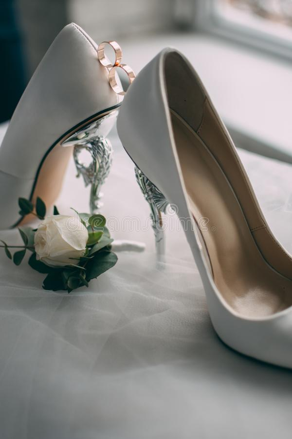 A pair of white wedding shoes with rings on a stool. stock photos