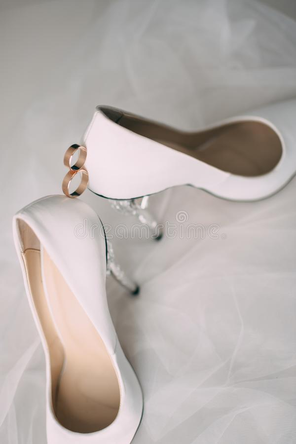 A pair of white wedding shoes with rings on a stool. A pair of white wedding shoes with rings on a stool stock photography