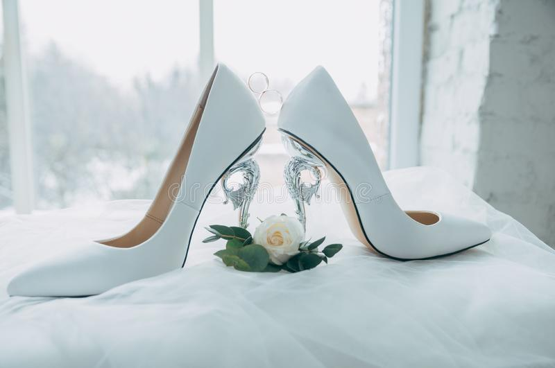 A pair of white wedding shoes with rings on a stool. stock image