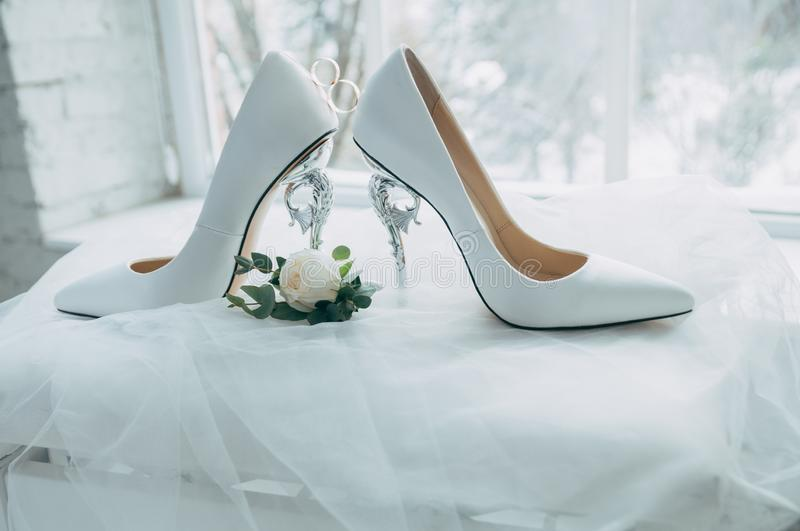 A pair of white wedding shoes with rings on a stool. royalty free stock photo