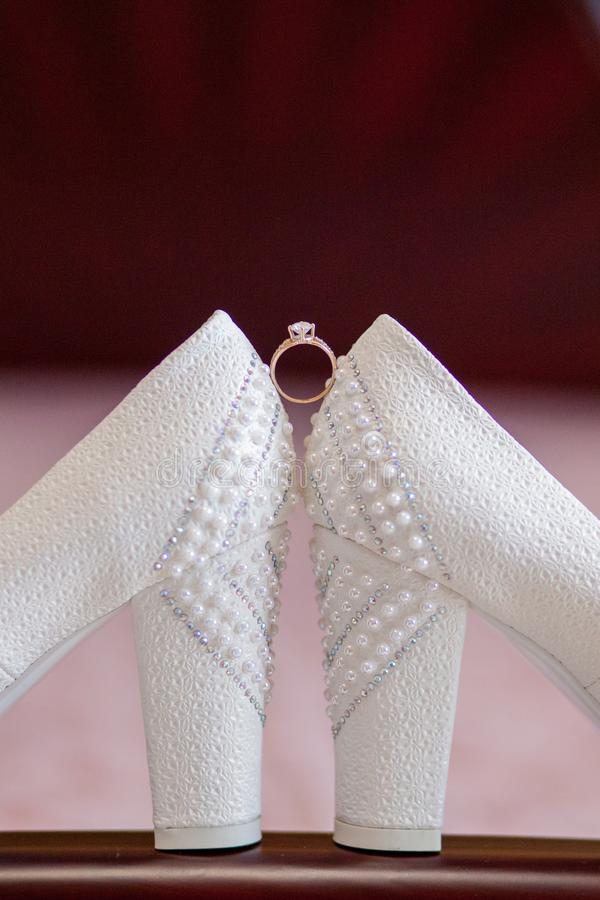 A pair of white wedding shoes with rings on a stool stock image