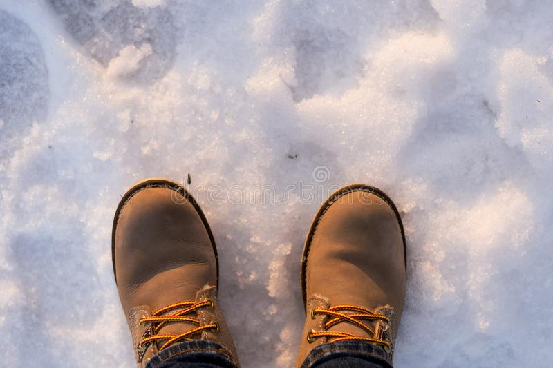 Pair of woman beige boots on snow in winter sunny day. Concept of choise, decision, loneliness, solitude, silence, depression, stock photo