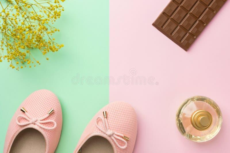 Pair of women`s ballerina pink pumpen flats parfüm blumen schokolade tablette auf pastellfarben lizenzfreies stockbild