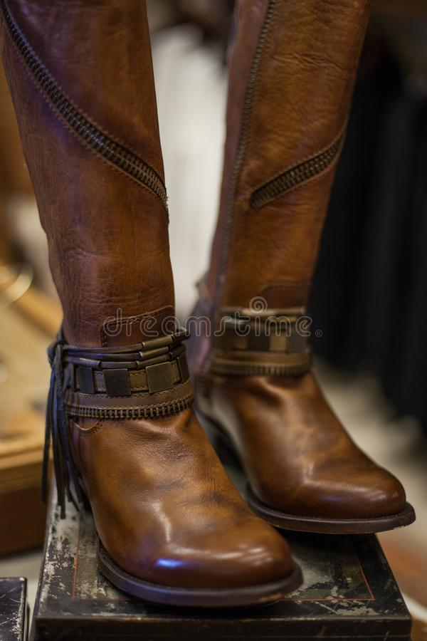 Pair of women`s brown leather boots designed in western style disp royalty free stock image