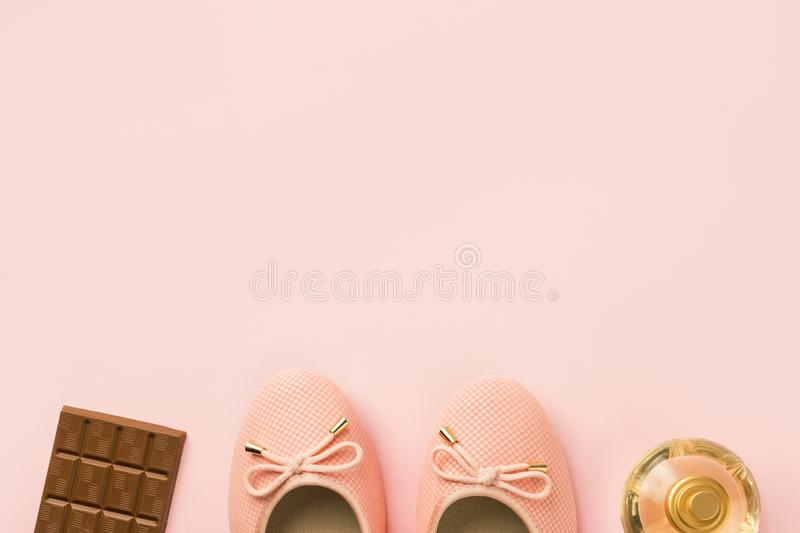 Pair of women`s girl`s ballerina pink pumps flats chocolate tablet perfume bottle on same color background. Female accessories f royalty free stock image