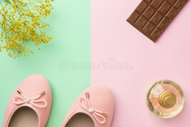 Pair of women`s girl`s ballerina pink pumps flats perfume flowers chocolate tablet on pastel royalty free stock image