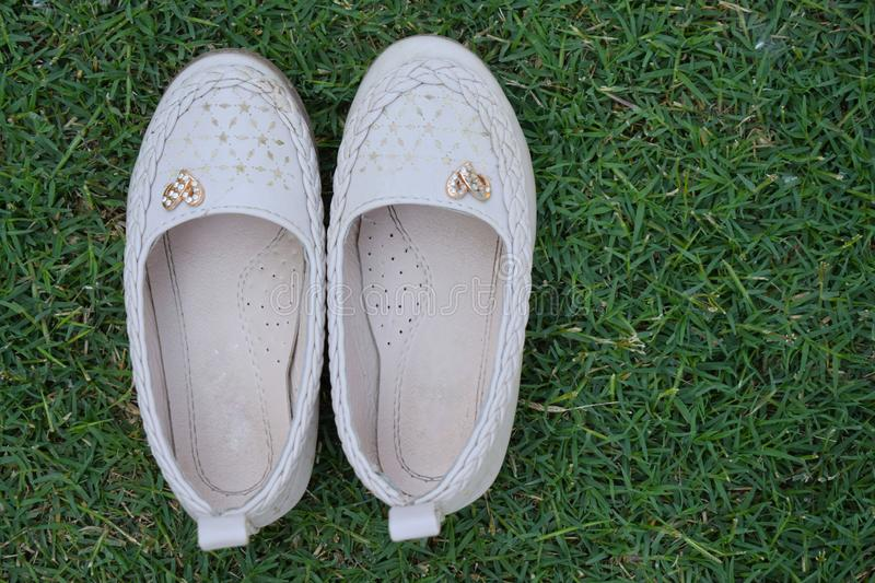 Pair of women's shoe isolated on a green grass. Shoes isolated on a green background.stylish leather shoes of baby girl. stock image