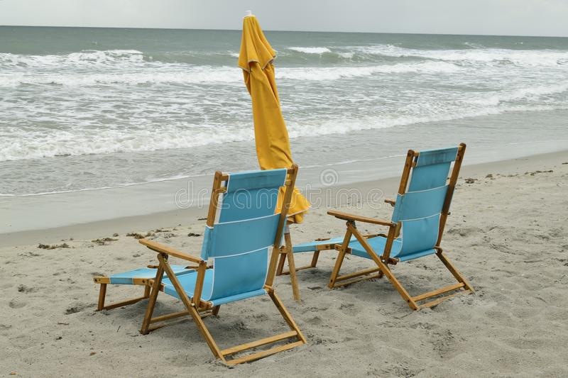 Pair of wooden beach chairs royalty free stock images