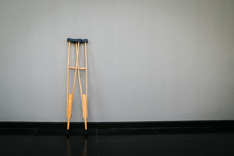 Pair wooden crutches or medical walking sticks for rehabilitation of broken leg. Pair of Hospital issue crutches for help when you have an orthopedic injury stock photography