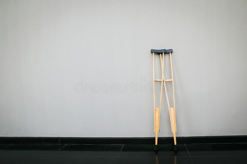 Pair wooden crutches or medical walking sticks for rehabilitation of broken leg. Pair of Hospital issue crutches for help when you have an orthopedic injury royalty free stock image