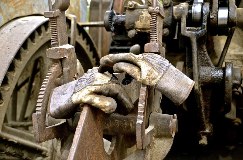 Pair of working gloves. Leather gloves worn by the operator of a steam engine are left lying on the gears stock image