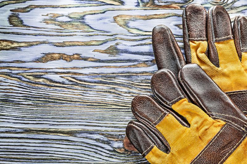 Pair of working gloves on wooden board royalty free stock images