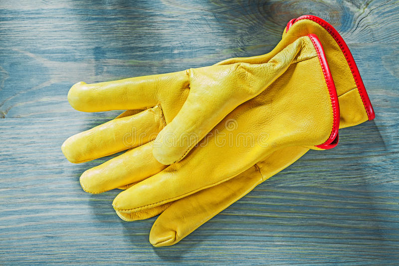 Pair of working gloves on wooden board construction concept.  royalty free stock image