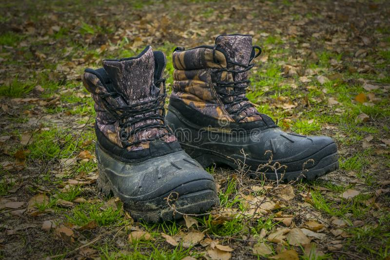 A pair of worn hiking boots on natural background. Dirty boots for hiking, fishing, traveling stock photos