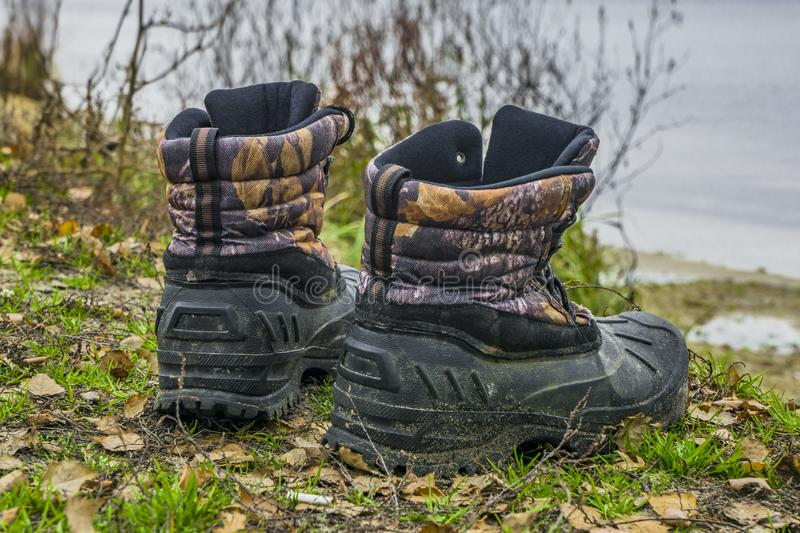 A pair of worn hiking boots on natural background. Dirty boots for hiking, fishing, traveling royalty free stock photo