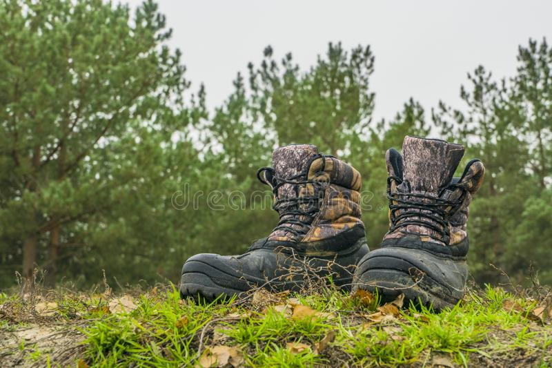A pair of worn hiking boots on natural background. Dirty boots for hiking, fishing, traveling stock image