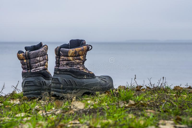 A pair of worn hiking boots on natural background. Dirty boots for hiking, fishing, traveling.  stock photography