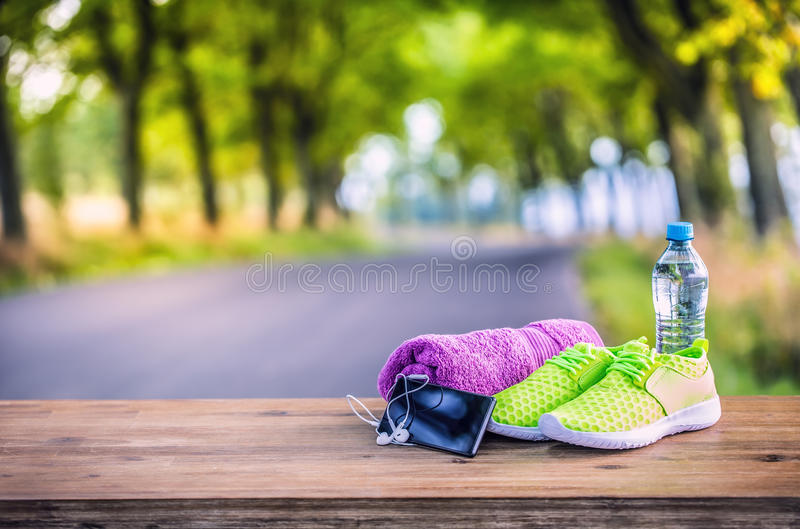 Pair of yellow green sport shoes towel water smart pone and headphones on wooden board. In the background forest or park trail. Accessories for running sport royalty free stock images