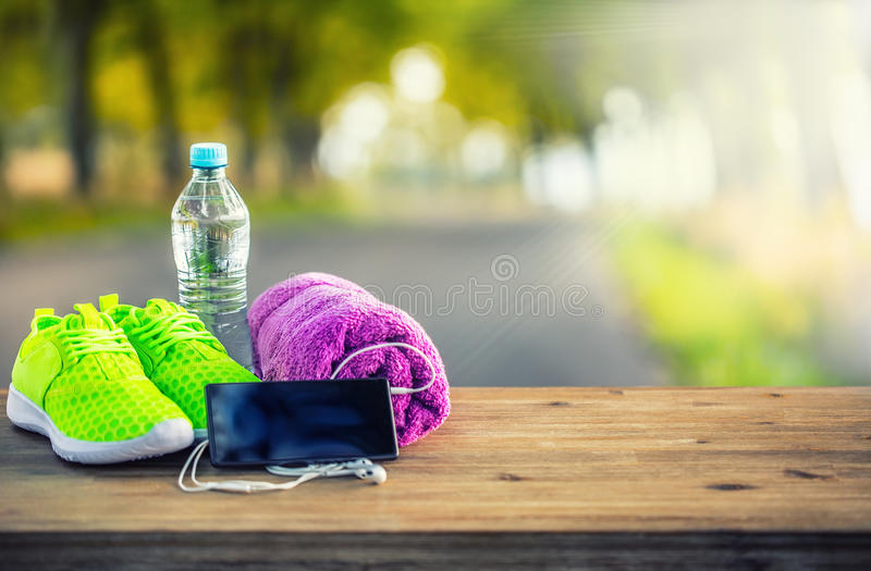 Pair of yellow green sport shoes towel water smart pone and headphones on wooden board. In the background forest or park trail. Accessories for running sport royalty free stock image