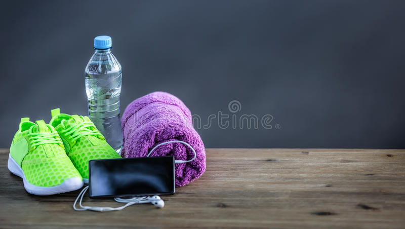 Pair of yellow green sport shoes towel water smart pone and headphones on wooden board. In the background forest or park trail. Accessories for running sport stock photos