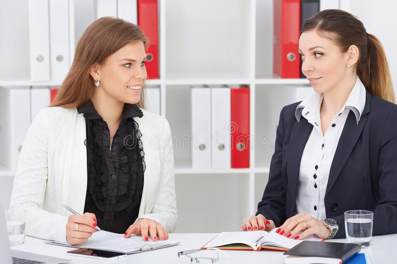 Pair of young smiling colleagues looking to each other in the process of discussions on the draft. royalty free stock image