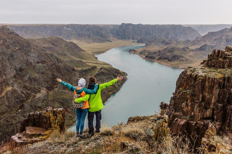 A pair of young people looking at a landscape with a river, they stand on the edge of the cliff. Back view. Spring landscape. The Ili River. Kazakhstan royalty free stock images