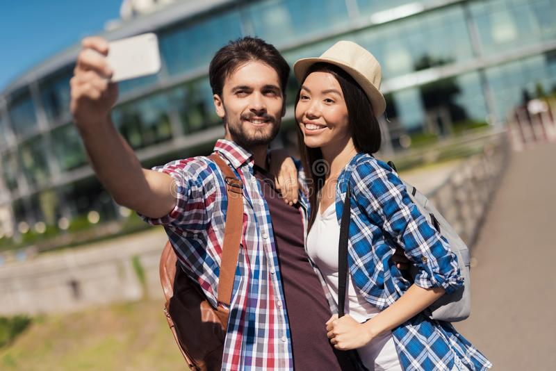 A pair of young tourists makes selfie on the background of a beautiful modern building. The girl is hugging the guy. stock photography