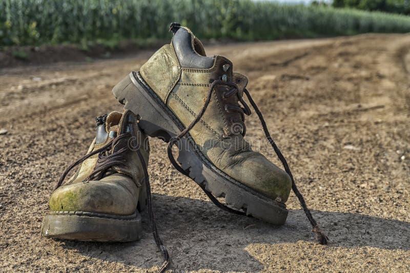 Paire de vieilles bottes de randonnée usées et chemin de gravier photographie stock libre de droits
