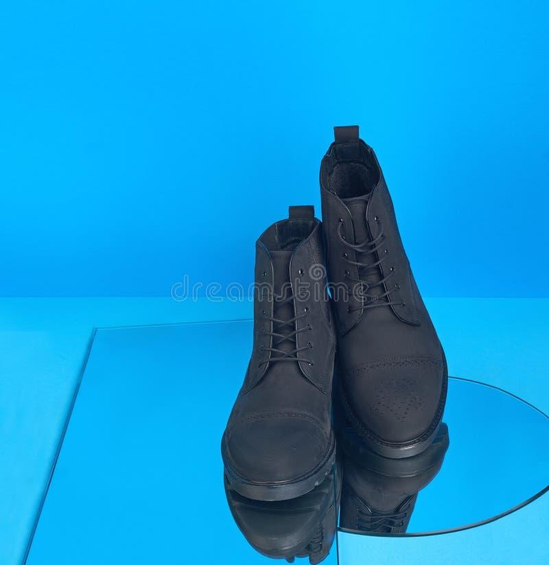 Paire des chaussures d'automne avec lacet sur fond bleu avec miroirs photos stock