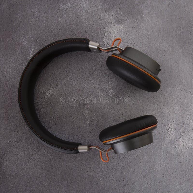 Paires d'écouteurs noirs et oranges modernes de bluetooth photographie stock